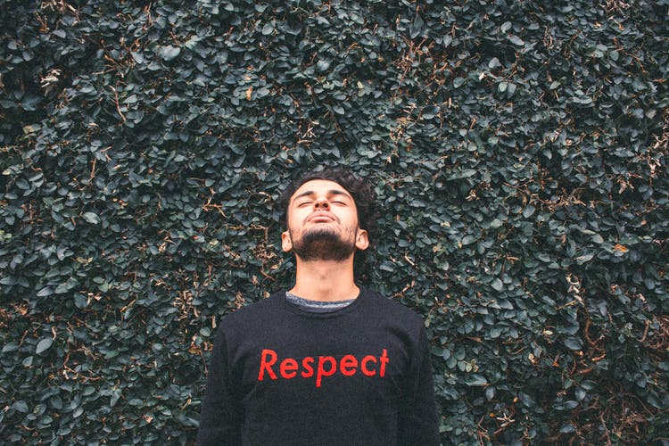 Man with closed eyes and a t-shit that says respect